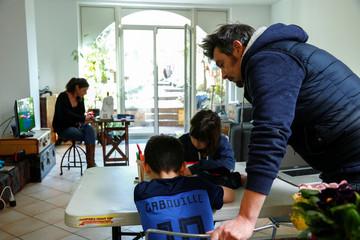Belgian freelance graphic designer Joel Kockaert supervises school homework of his son Gabriel next to the neighbour's daughter, Alina, during the coronavirus lockdown, in Brussels