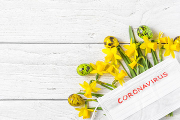Coronavirus quarantine during Easter holidays. spring narcissus flowers with face medical mask and eggs. flat lay
