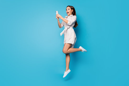 Full length profile photo of pretty shocked lady freelancer jumping high up hold telephone arms read positive blog comments wear spring striped mini dress isolated blue color background