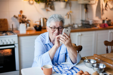 Senior woman using mobile phone at cozy home kitchen. Retired person shopping online. People...