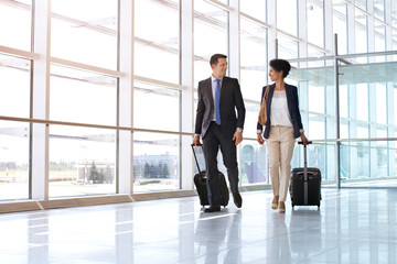 Businessman and businesswoman walking on airport.