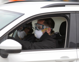 Two men wearing masks drive up for assessment as the city's public health unit holds walk-in testing for coronavirus disease (COVID-19) in Montreal
