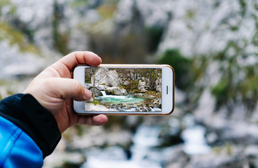 Bright photo of mountain waterfall and turquoise lake flowing into river on smartphone in hand on crop unrecognizable tourist in peaks of Europe, Asturias, Spain