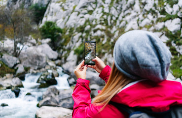 Bright photo of mountain waterfall and turquoise lake flowing into river on smartphone in hand of crop unrecognizable woman tourist in peaks of Europe, Asturias, Spain