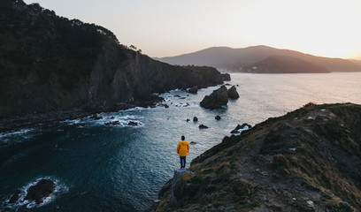 Papiers peints Cote From above back view of person in vibrant yellow jacket standing on edge of cliff and enjoying amazing scenery of rocky sea coast during sunset in Spain