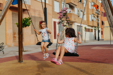 Full length little girls sitting together on swing and looking away while resting on playground on sunny summer day