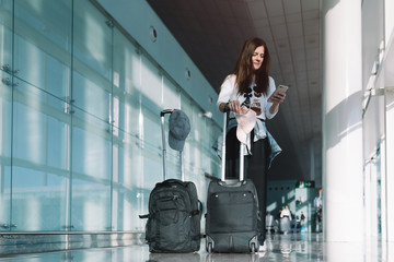 From below of young female in casual wear with luggage surfing smartphone waiting for departure in airport