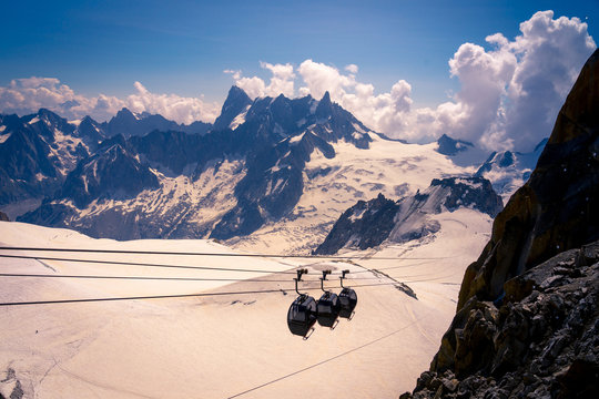 From above covered cabins moving down cable car in white snowy mountains in bright cloudy day in  Chamonix, Mont-Blanc