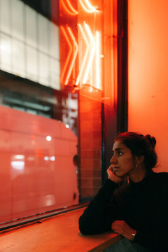 Side view of gorgeous young ethnic woman looking out window with red lightening on the background leaning on hand and dreaming