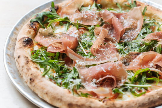 Top view of tasty pizza with thin slices of bacon and fresh greenery on plate in restaurant