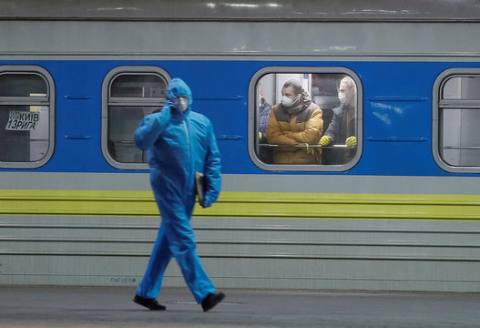 Employee wearing a protective suit walks past the train which evacuated Ukrainian citizens from Latvia, in Kiev