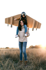 Happy cute boy wearing goggles and cardboard wings while sitting on mother shoulders and imitating aviator on meadow in backlit