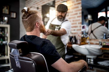 Barber trimming beard of redhead man sitting in barbershop