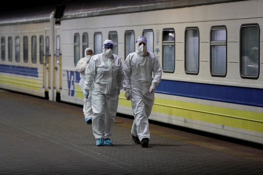 Employees wearing a protective suits walk past the train which evacuated Ukrainian citizens from Latvia, in Kiev