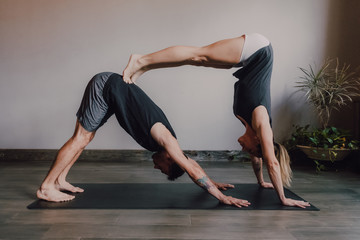 Side view of young barefooted man and focused woman in sportswear doing balance exercise standing in dog pose while training together on floor in light contemporary workout room