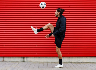 Man playing soccer ball on street
