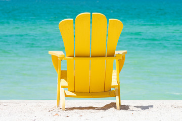 Yellow Adirondack chair with tropical view of emerald water