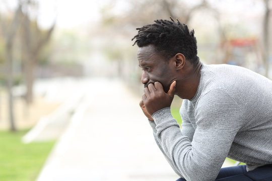 Pensive serious black man looking away on a park