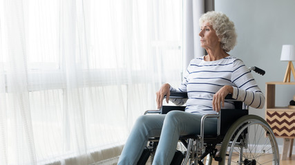 Pensive sick disabled old lady sit in wheelchair look in distance feel lonely at home or retirement house, thoughtful sad handicapped mature woman in wheel chair thinking, elderly disability concept