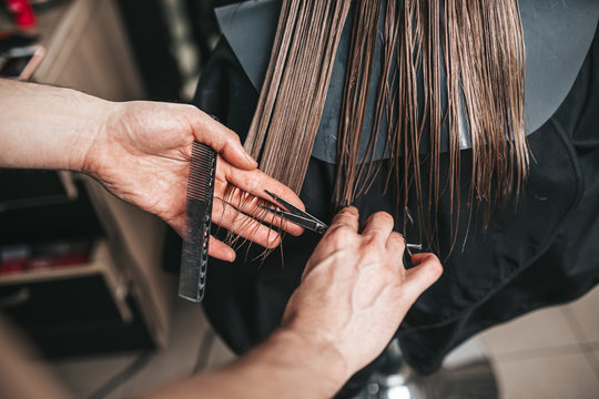 Young woman in hairsalon getting rid of split ends. Haircut.