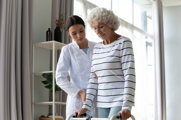 Fotomurales - Young female nurse help old lady patient with walking frame in home or hospital, woman doctor or caregiver assist senior elderly grandmother with walker, physiotherapy, rehabilitation concept