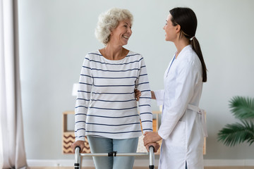 Fotomurales - Happy senior handicapped woman stand hold walking frame talk with positive caring female nurse or caregiver, smiling mature older lady with walker speak with young doctor, elderly healthcare concept
