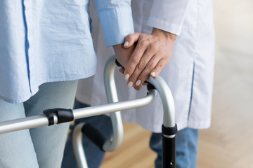 Fotomurales - Close up of woman doctor help disabled mature patient with walking frame, caring female nurse or caregiver assist senior old lady standing using walker, physical therapy, rehabilitation concept