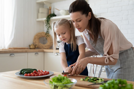 Young mother teach little preschooler daughter chop vegetables preparing salad for lunch together, loving mom and small girl child cooking dinner together, kid helping mommy with food preparation