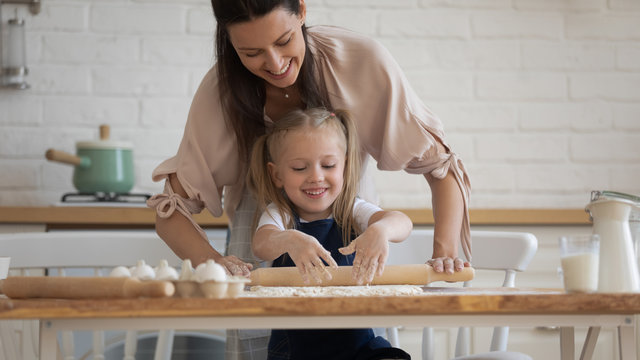 Smiling young mum teach excited little daughter make dough work use roller pin preparing pastries in kitchen together, happy mother cooking baking buns or pie with small preschooler child