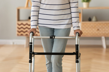 Fotomurales - Close up of sick disabled senior woman standing making steps holding walker in rehabilitation center, mature ill handicapped old lady walk with walking frame in clinic, physiotherapy concept