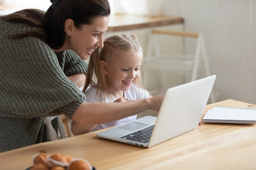 Happy young mother and cute preschooler daughter watch funny video on laptop together, smiling mom or nanny and little girl child have fun playing game on computer or studying learning online