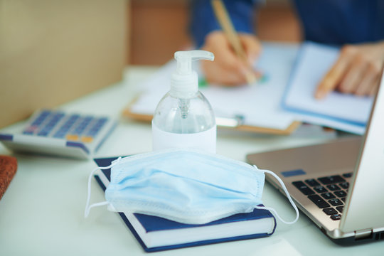 medical mask and hand disinfectant on table in home office