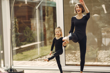 Girl is engaged in gymnastics. Family in a yoga studio. Kid in a black sportwear.