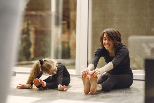 Girl is engaged in gymnastics. Family in a yoga studio. Kid in a black sportwear.
