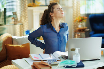 tired woman in modern house in sunny day having back pain