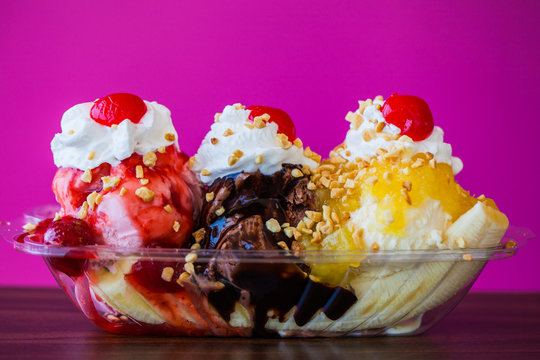 Banana split ice cream with cherries on top against pink wall