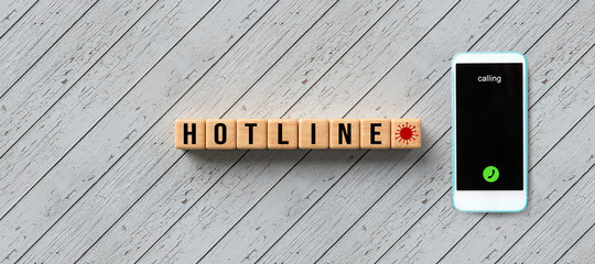 cubes with text HOTLINE and smartphone on wooden background