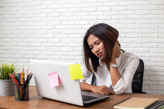 Business woman suffering from Neck pain in office