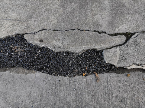 Repairing concrete surfaces with asphalt