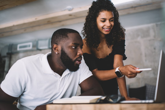Smiling dark skinned female 20s explaining information to male student pointing on web page on laptop computer, surprised african american man amazed with browsed video communicating with girlfriend