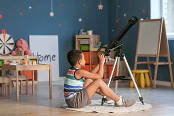Little African-American boy with telescope looking at stars in evening Fotomurales