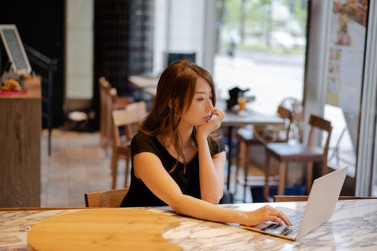 テレワーク / カフェでラップトップ(ノートパソコン)を見ている若い日本人女性 / Young Japanese woman looking at laptop in cafe 自粛, おうち時間, 読書 stayhome  リモートワーク