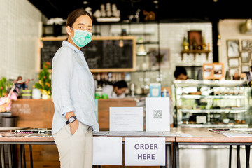 Woman in protective mask buying food and beverage in cafe to takeaway.