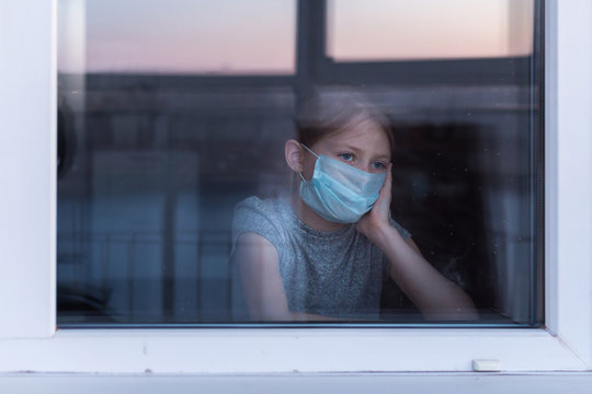 Stay at home quarantine coronavirus pandemic prevention. Sad child in protective medical mask looks out window. View from street. Prevention epidemic.