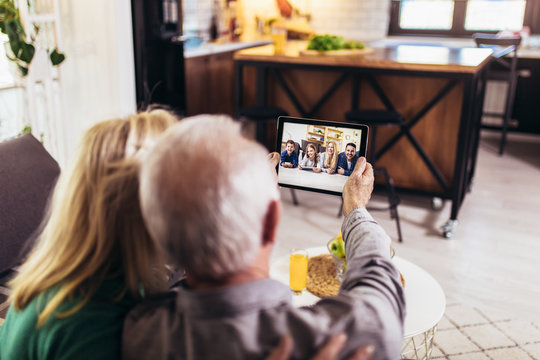 Senior couple making video call on digital tablet with their grandchildren and children.Quarantine. Health concept.