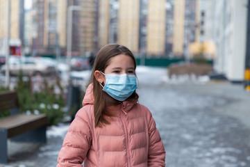 Coronavirus protection. A caucasian girl wearing protective mask walking on a street