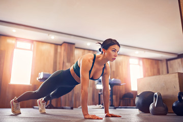 young motivated girl doing plank exercise at gym, full length photo, copy space.