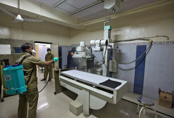 A municipal worker disinfects an X-ray machine inside a government-run hospital to limit the spreading of coronavirus disease (COVID-19), in Mumbai