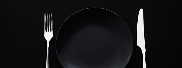 Empty plates and silverware on black background, premium tableware for holiday dinner, minimalistic design and diet
