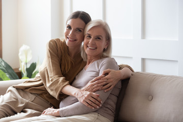 Portrait happy adult daughter and older mother hugging and holding hands, sitting on couch at home,...